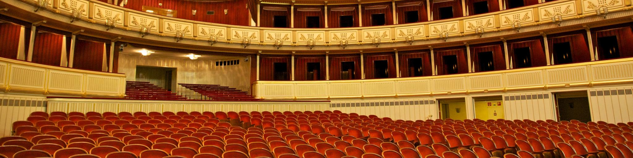 Red seats lined up in the audience of the grand Vienna State Opera House in Austria