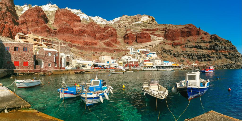 Fishing boats float in the Old port Amoudi of Oia village at Santorini island in Aegean sea, Greece