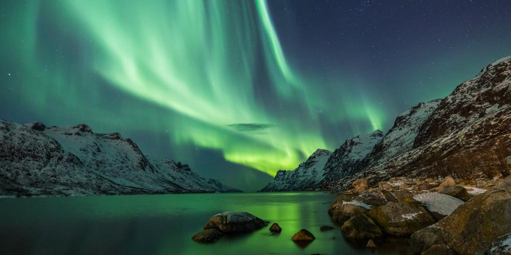 Green Northern Lights over the mountains and water in Iceland.