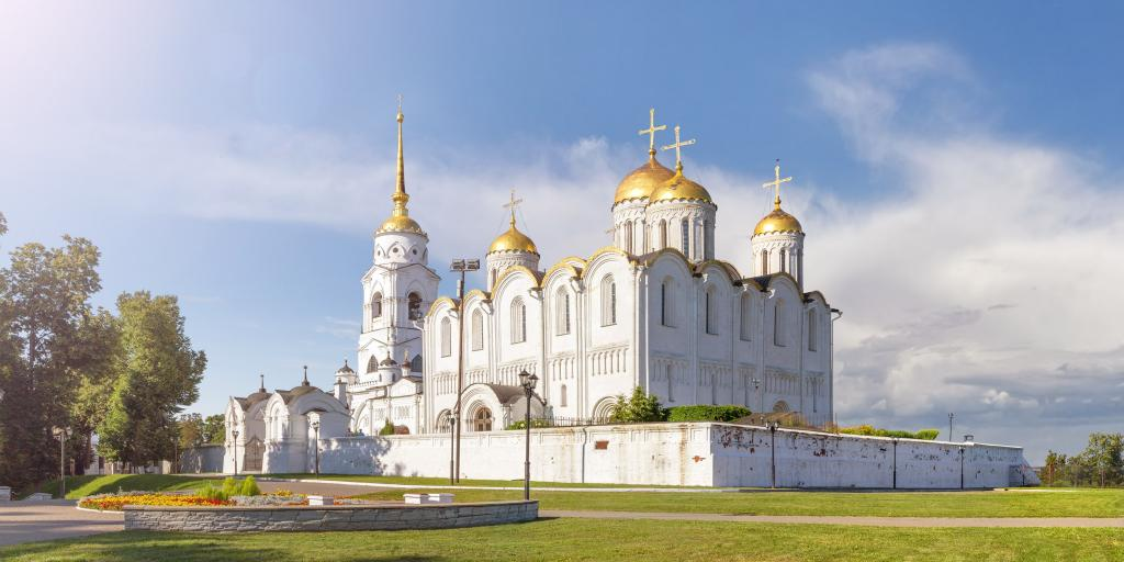 The outside of the white-stone Holy Dormition Cathedral in Vladimir, Russia,  with its golden roofs looking bright, on a sunny day