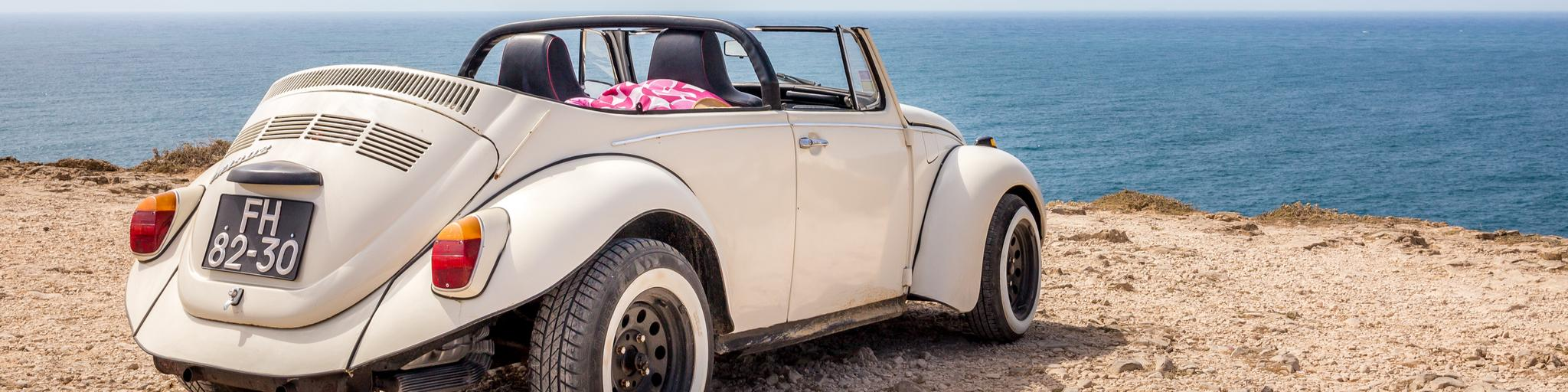 A classic car parked on a ledge overlooking the sea in Cape St Vincent in Portugal