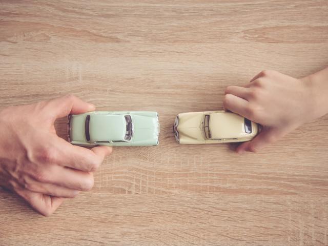 Top down view of a dad and son's hands playing toy cars