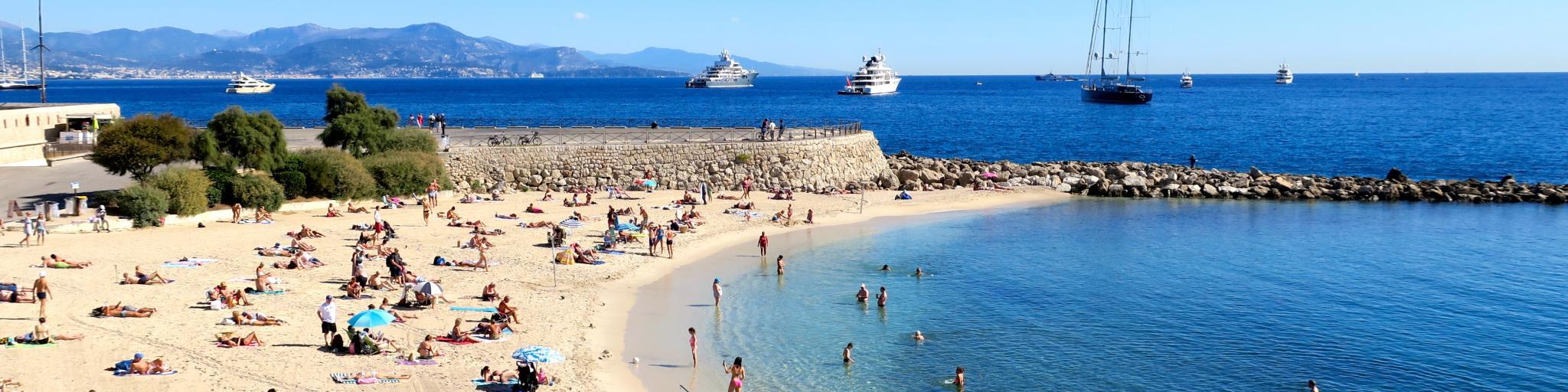 Holiday makers relax on a sandy beach in Antibes, France, on a sunny day