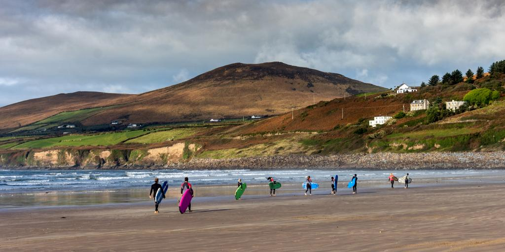 Surfers walking down Inch Beach in Ireland carrying their boards