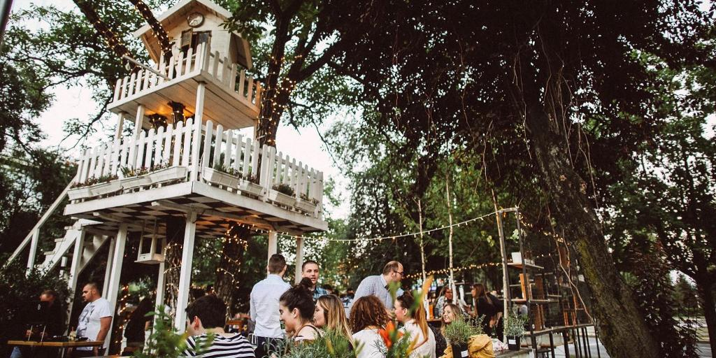 People sitting under a treehouse at Zagreb's A most unusual garden cafe