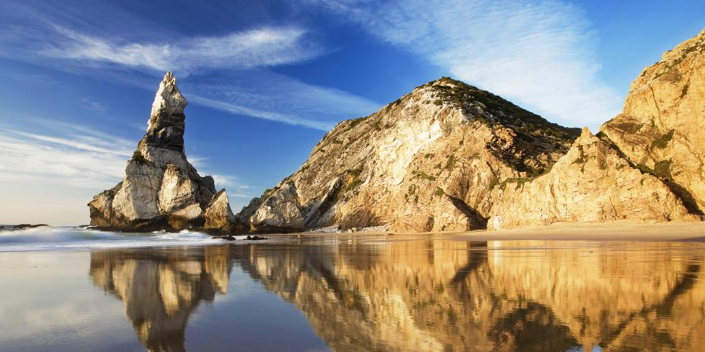 Rocks reflecting on the wet sand at Praia da Ursa beach, Portugal