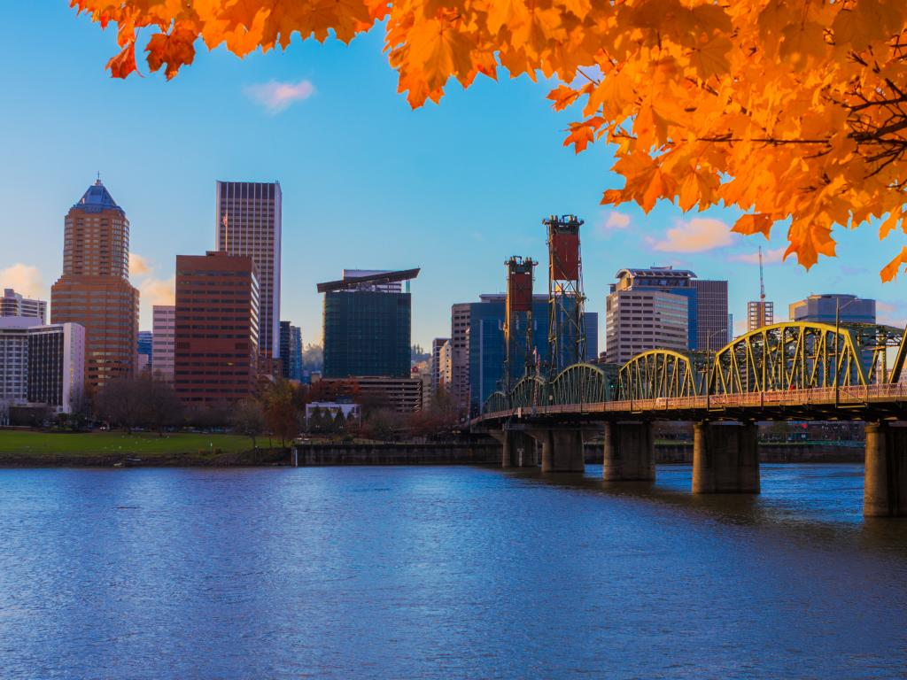 View of Portland downtown from across the Willamette River in the fall with bright orange leaves