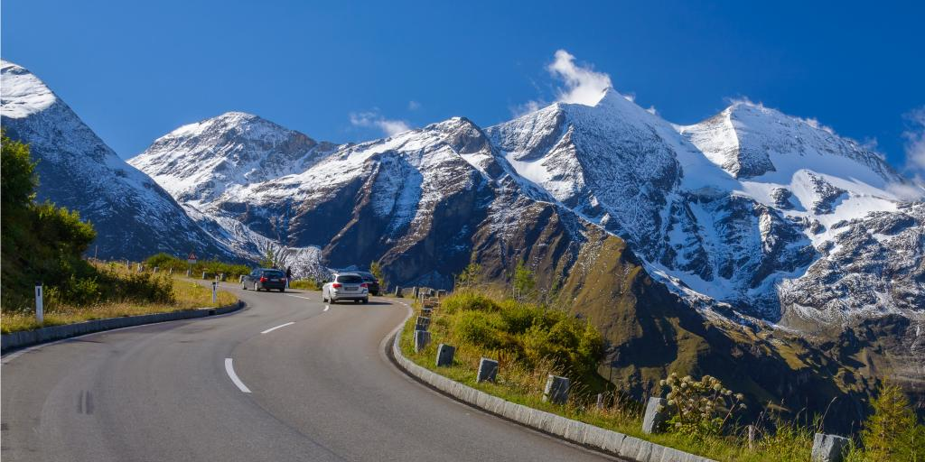 A car driving on the Grossglockner High Alpine Road, Austria with snowy peaks in the distance