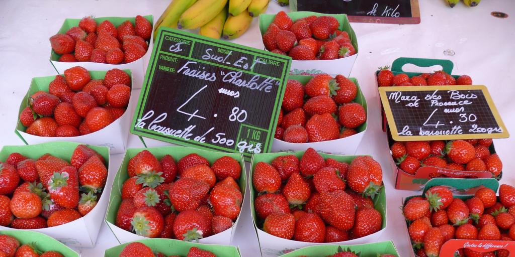 Punnets of strawberries and a price board at the Cours Saleya markets in Nice, France