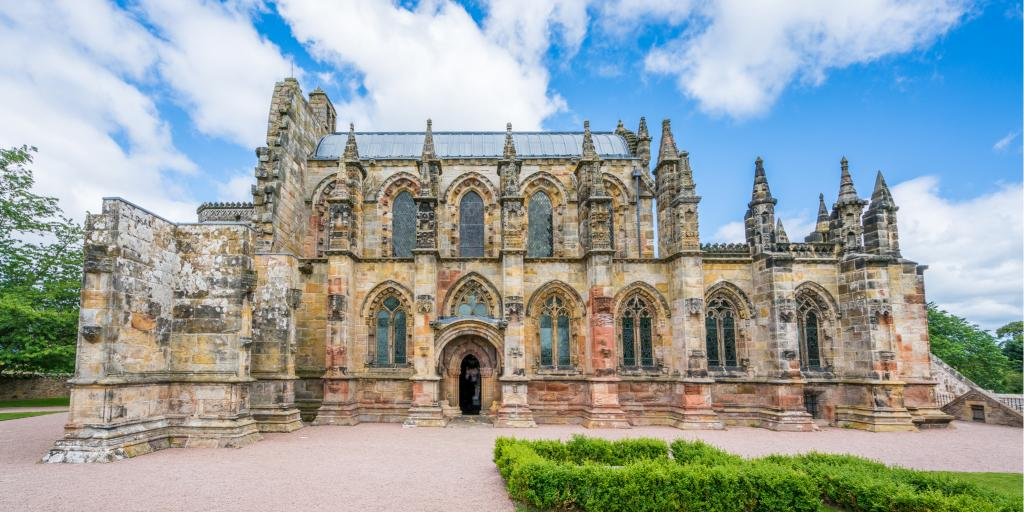 Rosslyn Chapel in the Scottish village of Roslin on a sunny day with blue sky and some clouds