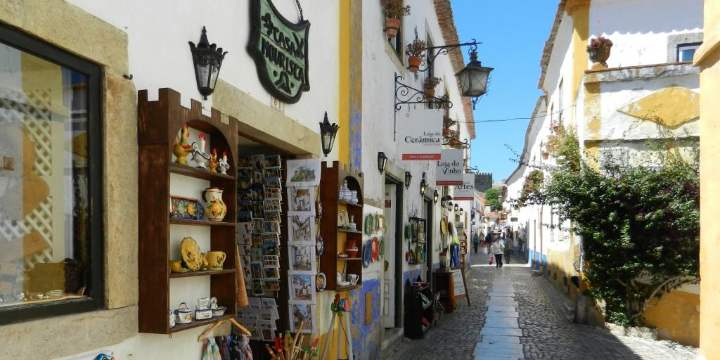 Cobbled street with gift shops in Obidos, Portugal
