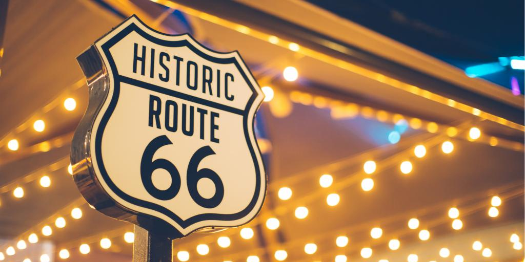 Route 66 road sign in front of fairy lights in the USA