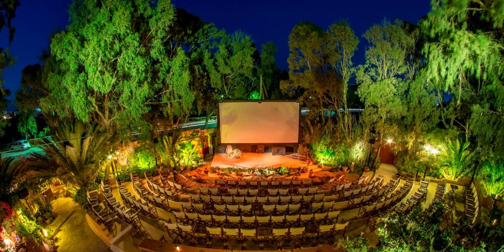 Chairs line up in a U shape in front of a giant screen at Open Air Cinema Kamari
