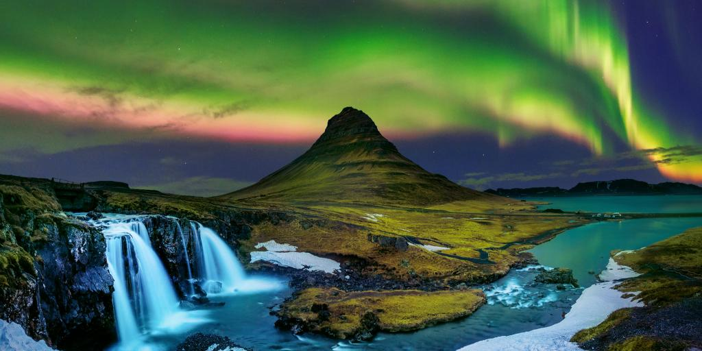 Northern lights in the Iceland sky above a waterfall