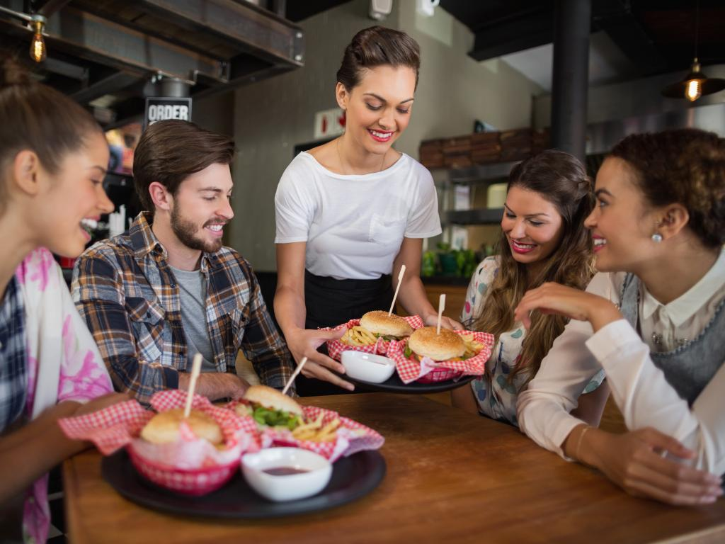 Waitress serving food to a table of friends in a restaurant