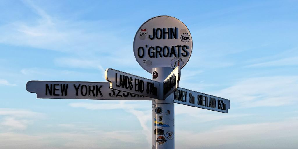 The signpost at John O'Groats with arms pointing towards New York, Lands End and Orkney & Shetland and a blue sky in the background