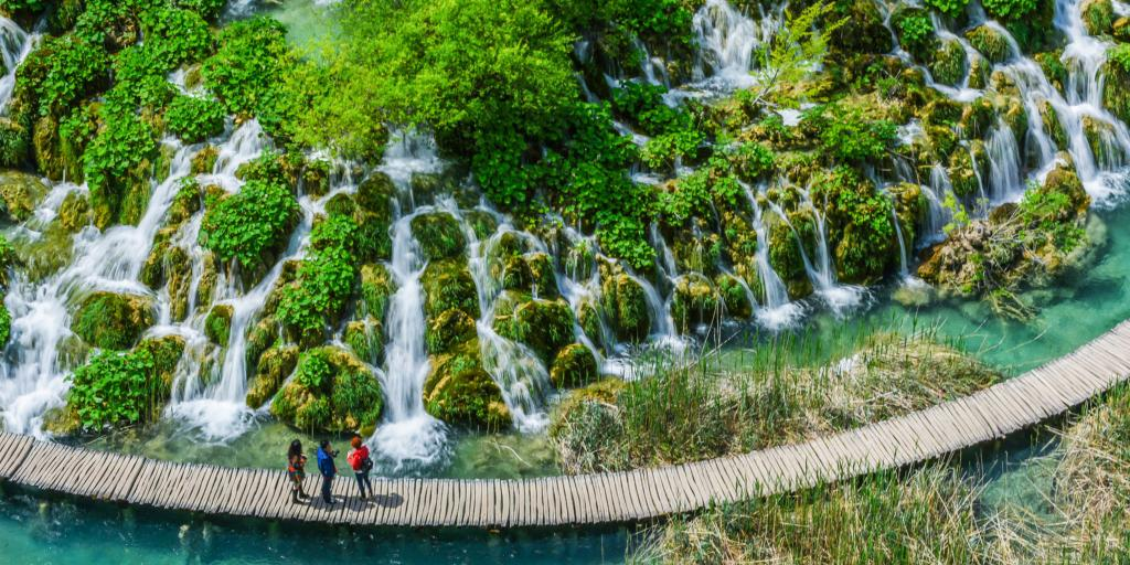 People on a wooden walkway looking at the waterfalls in Plitvice Jezera, Croatia