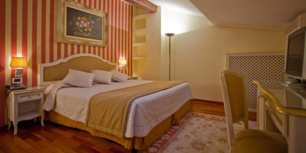A bedroom with red and yellow striped walls and a skylight at Hotel Porta San Mamolo in Bologna