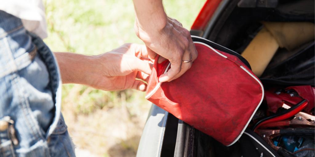 A man loading a car first aid kit into his car