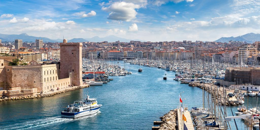 View over the Vieux port in Marseille, France, with lots of boats to the right and Saint Jean Castle to the left