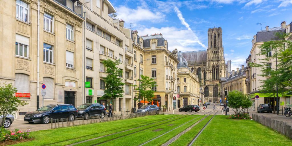 A street in Reims, France, with big stone buildings to the right and tram tracks surrounded by grass