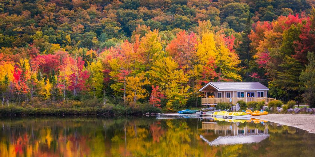 Boathouse surrounded by autumn trees, reflecting in Echo Lake, in Franconia Notch State Park, New Hampshire