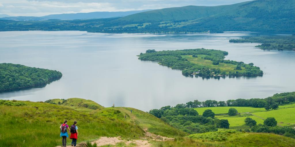 Two hikers walk on a hill overlooking Loch Lomond in Scotland