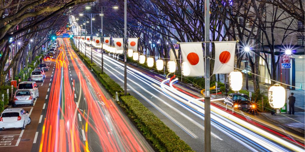 Blurred headlights of cars driving at night in Japan