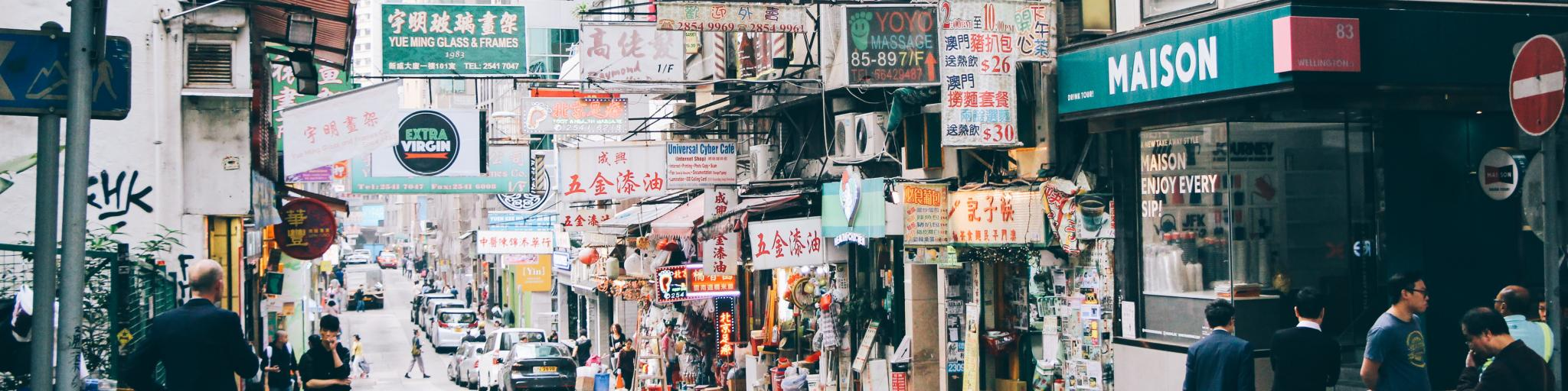 A street filled with signs and people in Hong Kong