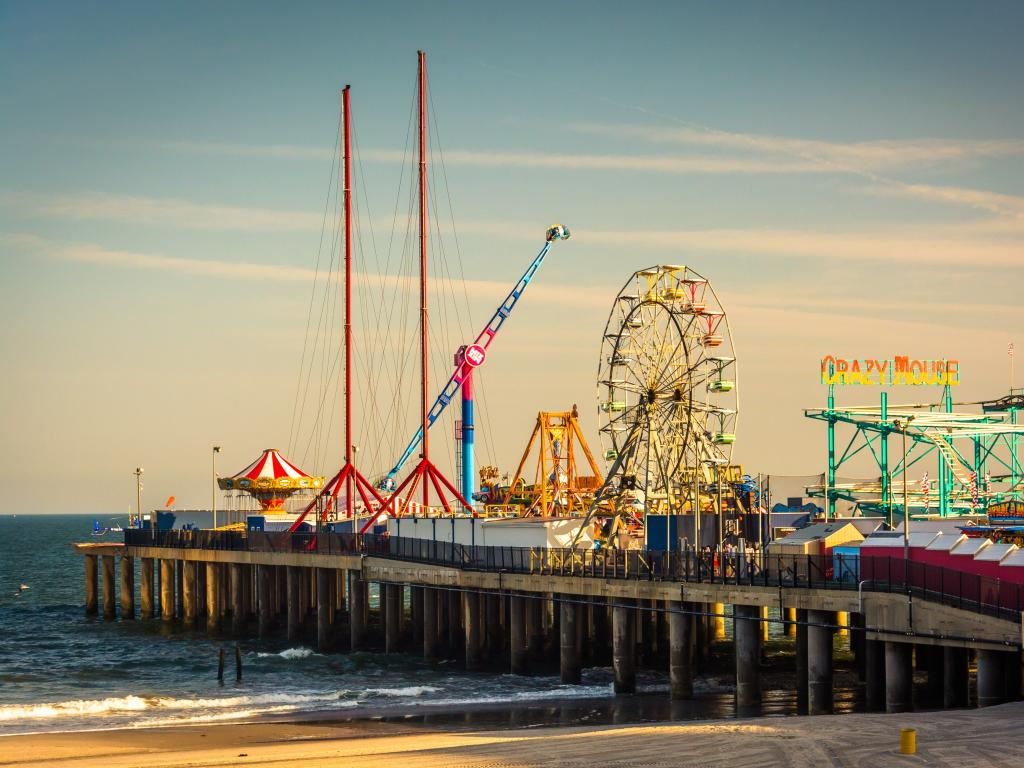 A fairground on a pier in Atlantic city, with a ferris wheel and rollercoaster most visible