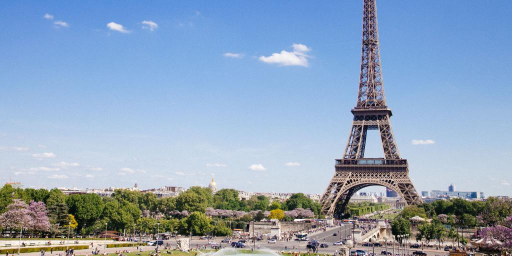 The Eiffel Tower of Paris stands tall on a sunny day in the French capital
