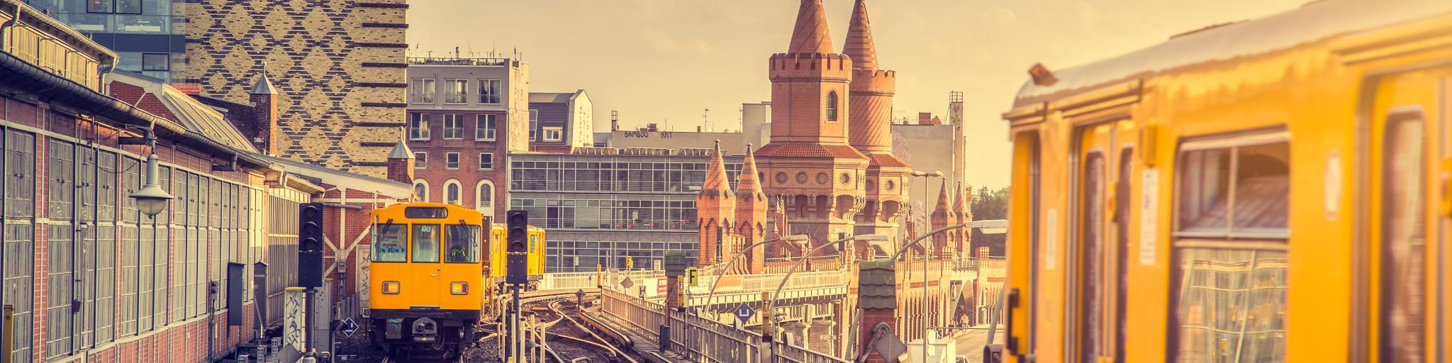 Panoramic view of yellow Berliner U-Bahn with Oberbaum Bridge, Berlin, in the background in golden evening light
