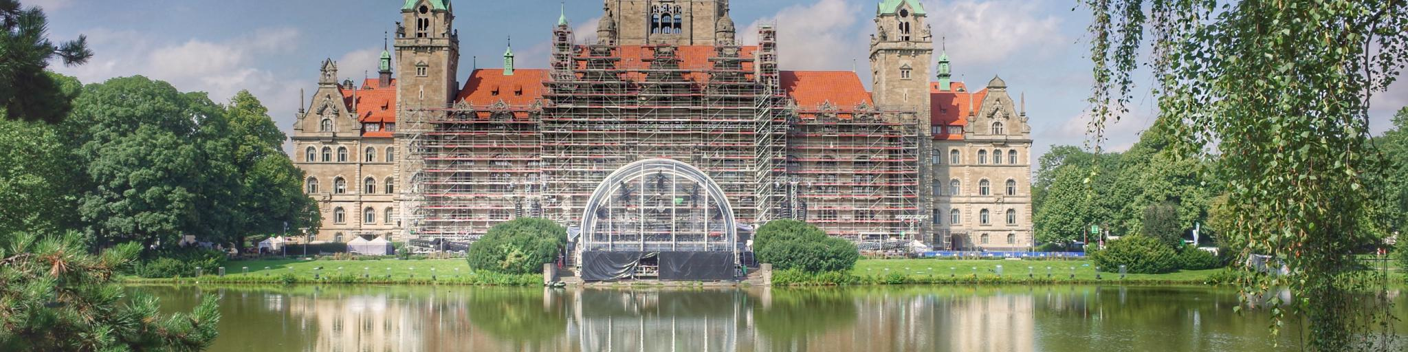 The castle-like New Town Hall sits in front of a lake in Hanover, Germany