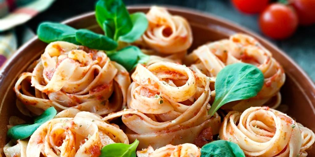 Bundles of tagliatelle pasta topped with tomato sauce and basil leaves