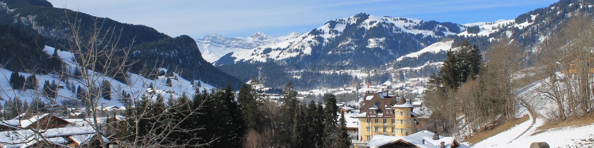 A bench overlooks the snowy ski resort town of Gstaad, Switzerland