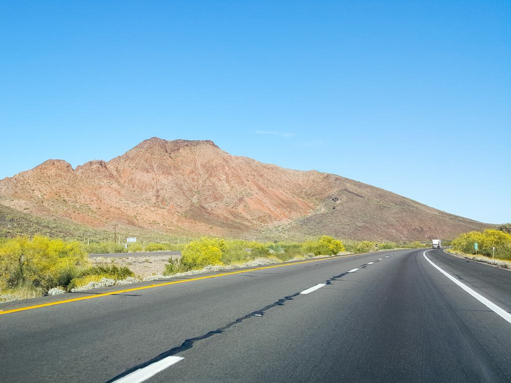 An empty highway of Interstate 10 with green bushes in the side along isolated hills and low rise mountain in Quartsize on a sunny weather