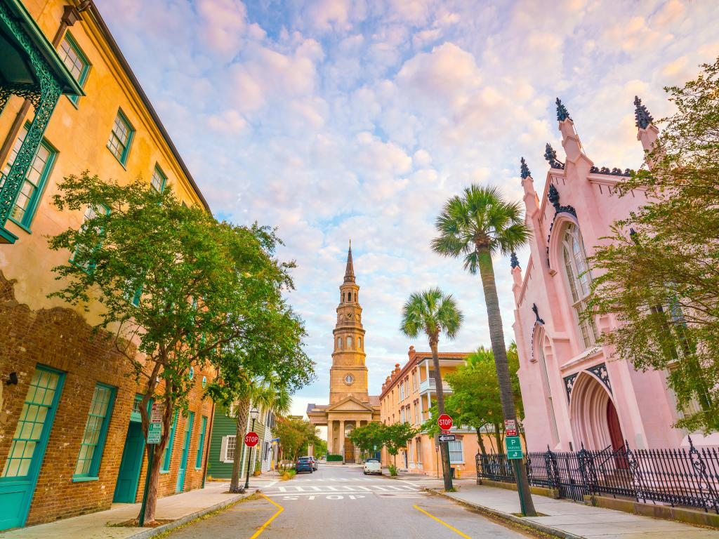 A scenic road with fascinating old buildings in pink, orange, green, and powder blue at twilight in the historic downtown of Charleston, South Carolina