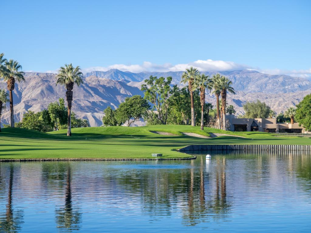 Palm trees, perfectly manicured lawns and water features of a golf resort in Palm Springs, California