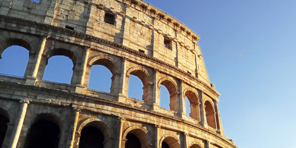 A close up of some of the arches of the Colosseum, Rome, against a blue sky