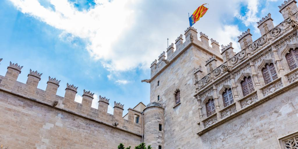 The stone building of Lonja de la Seda, in Valencia, Spain, with the battlements in view and a flag on top