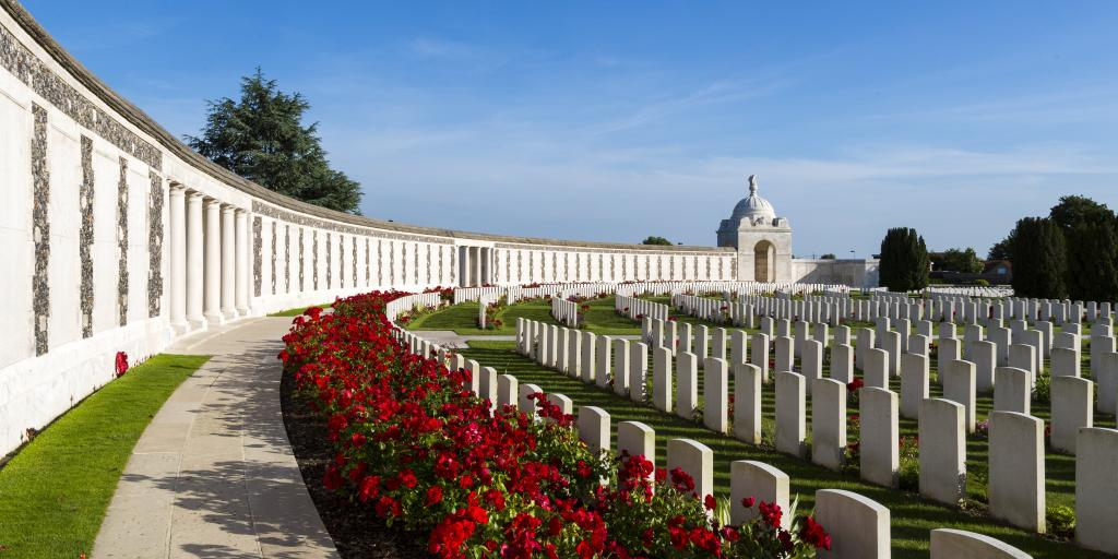 The curved wall of Tyne Cot cemetery, with rows of poppies and graves in front of it