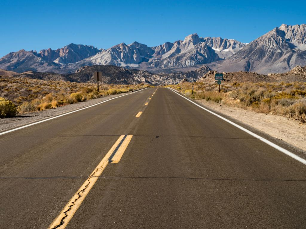A bright sunny day on an empty road to Inyo National Forest with a great view of the Eastern Sierra Nevada Mountains.