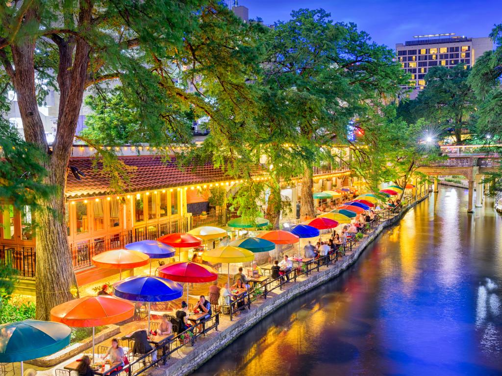 People eating dinner at tables set along the River Walk in San Antonio, Texas.