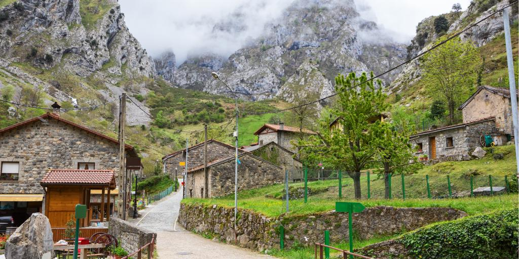 A road winds up through the mountain village of Cain on a cloudy day in Picos de Europa