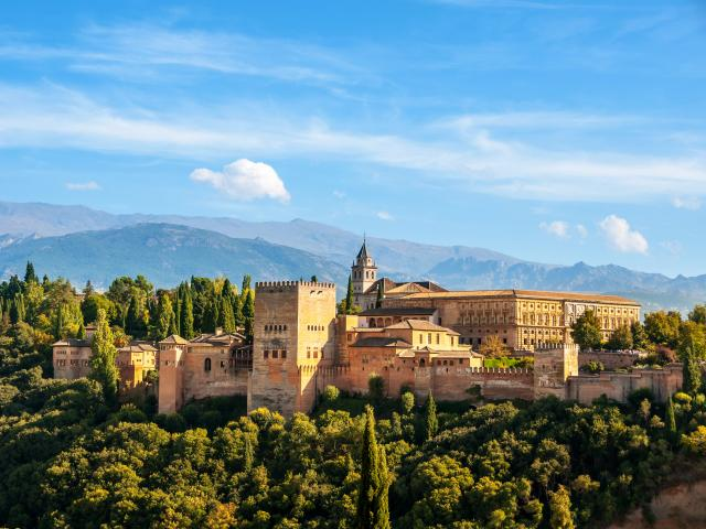 Aerial view of Alhambra Palace in Granada, Spain with Sierra Nevada mountains in the background, on a sunny day