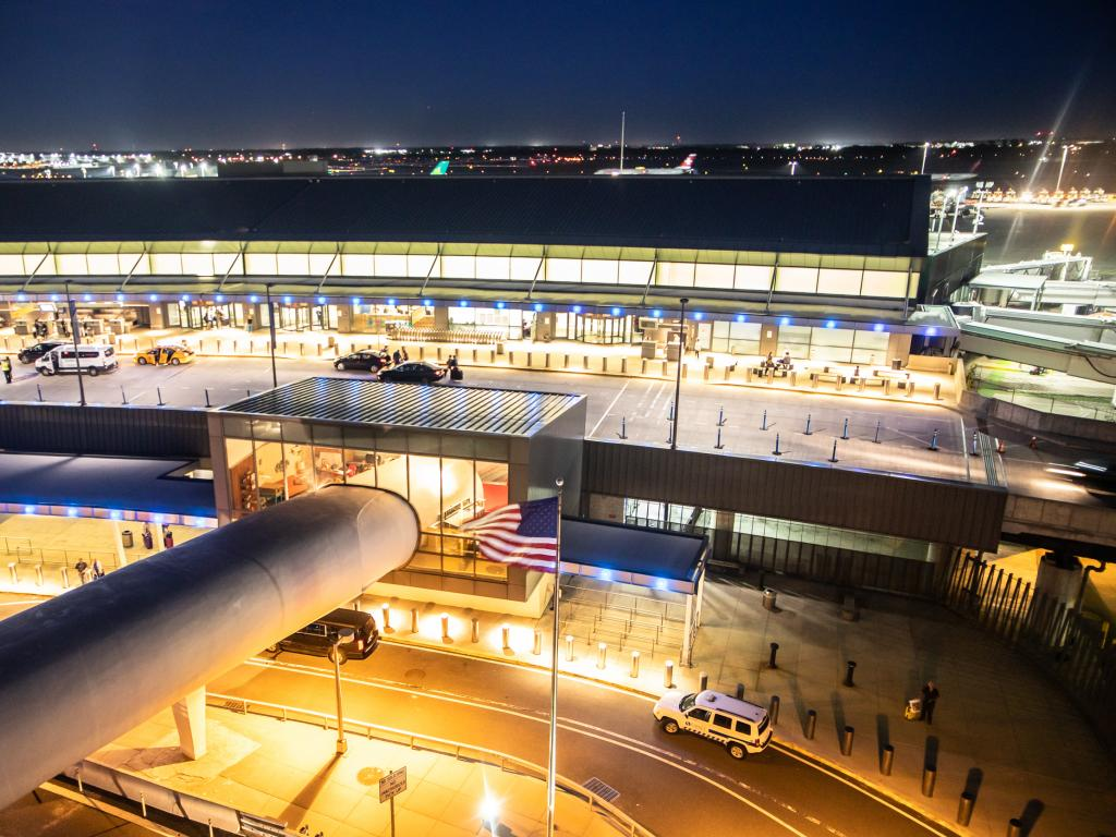 Top view of the entrance of John F Kennedy airport during the night with lights on. Some cars are on the road.