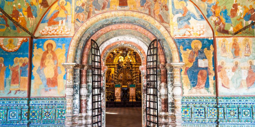 Arched internal doorway surrounded by colourful wall painting with icons in the Church of Elijah the Prophet in Yaroslavl, Russia