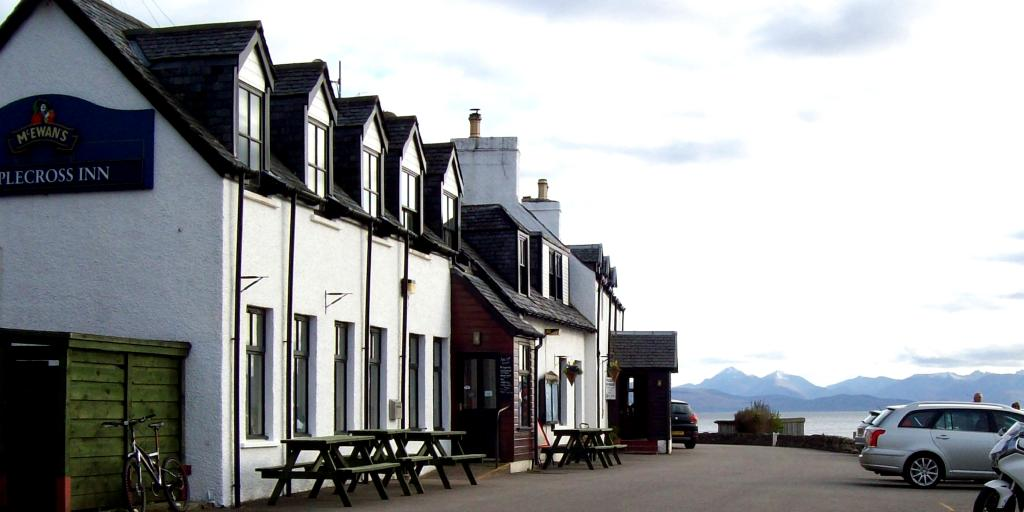The white exterior of the Applecross in with water and the mountains in the background, and a silver car to the right