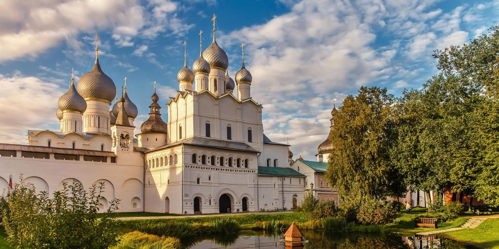 A view of the Rostov Veliky Kremlin with its silver domes and a garden in front of it, at golden hour