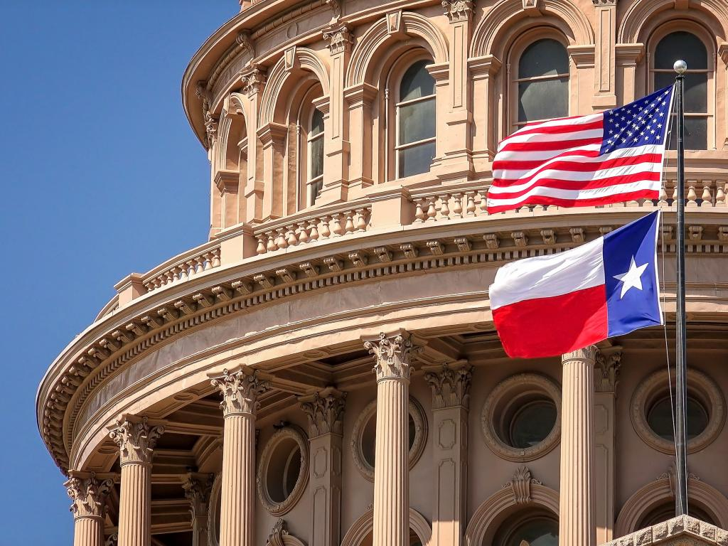 American and Texas State flags flying at the Texas State Capitol building in Austin
